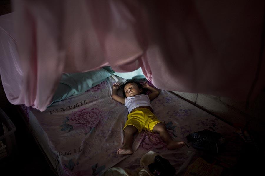 Una niña duerme en la casa en construcción en San Lorenzo de una de las familias desplazadas de El Pan. Foto: Periodistas Sin Cadenas
