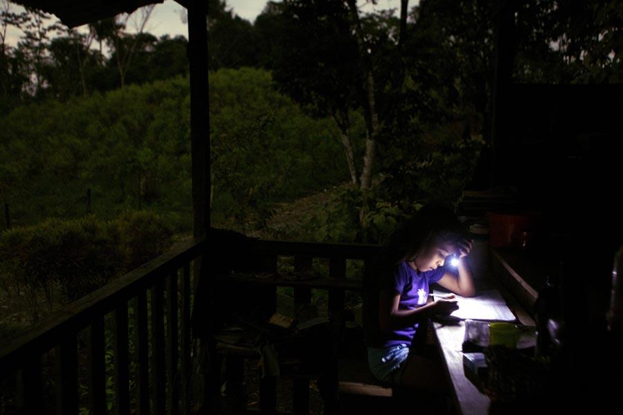 Una niña estudia en su casa en la mitad de las plantaciones de coca , en el área El Tandil.