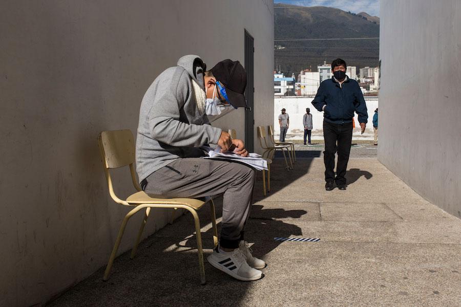 Un ciudadano busca el nombre del padrón electoral de su abuela entre los registros para ayudarla a sufragar.