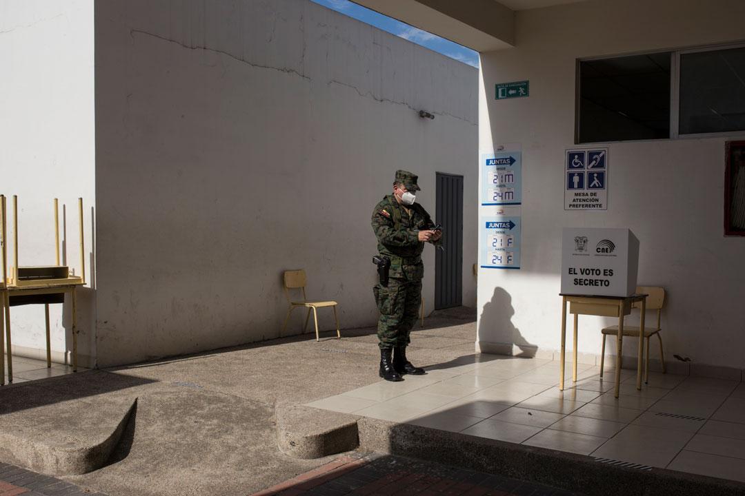 Un miembro de las fuerzas armadas, reporta a través de su teléfono celular cómo va la organización en la junta receptora del voto al que fue asignado.